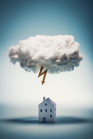 Paper house standing under a white cloud with yellow lightning. Natural distasters. Insurance concept. Stok Fotoğraf