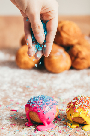Womans hand sprinkling sugar strands on colorful doughnuts. Decoration.