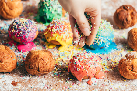 Womans hand sprinkling sugar sprinkles on colorful donuts. Decoration process.