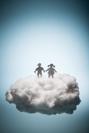 Two children standing on a white cloud. Eternal life. Christianity. Salvation concept. Stock Photo