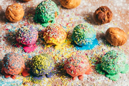 Couple of colorful sprinkled doughnuts laying in rows on a dirty kitchen counter. Stock Photo