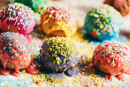 Colorful sprinkled donuts laying in rows on a messy kitchen counter. Delicious treats.