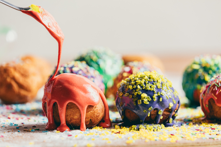 Orange glaze pouring from the spoon onto a doughnut. Sweet treats. Standard-Bild