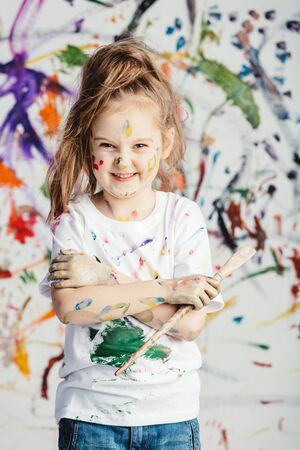 Smiling little girl with painting brush standing in front of messy background. Kid artist.
