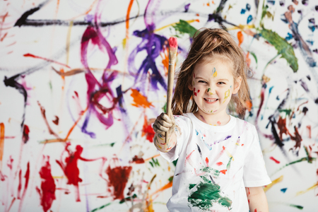Cute child with smuges of colorful paint showing a paint brush. Little artist. Stock Photo
