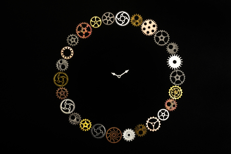 Simple clock made out of little cogwheels. Time concept. Clockwork. Stock Photo