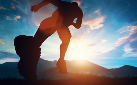 Man running towards the sunset in the mountains. Outdoor activities. Exercising and workout. Stock Photo