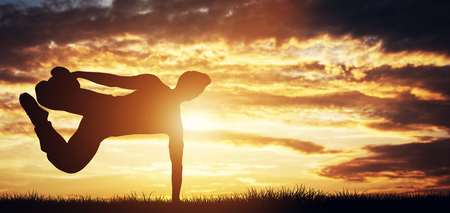 Young man exercising, doing stunts in the sunset. Parkour. Youth. Working out outdoors. Stock Photo
