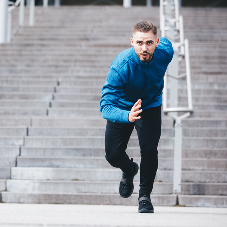 Handsome sportsman in athletic clothes, running fast. Sprinter. Fit lifestyle. Stock Photo