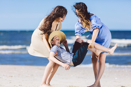 Two women carrying a boy in a straw hat on the beach. Family playtime. Bonding.