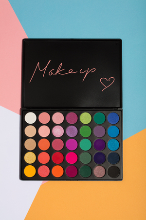 Makeup palette on a colorful geometrical background. MAKEUP writing and a heart.