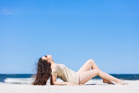 Young woman laying on the beach, sunbathing. Summer outdoor relax. Stock Photo