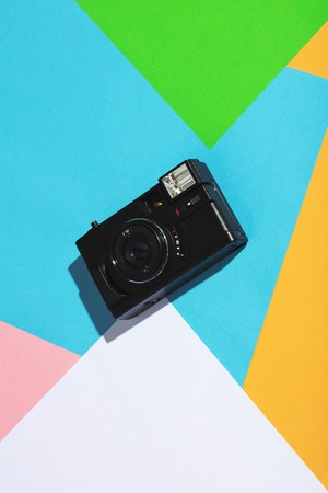 Vintage camera on a colorful geometrical background. Creativity. Vintage photo equipment.