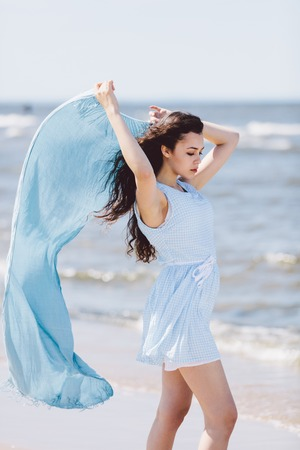 Young woman walking by the sea, holding a blue waving scarf. Summertime. Stock Photo