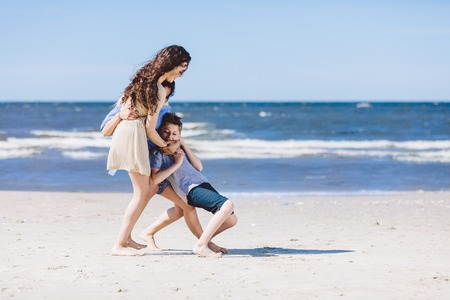 Mother and daughter playing with little brother by the sea. Family vacation. Summer break. Stock Photo
