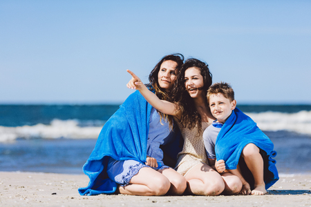 Family sitting on a sandy beach, older sister pointing her finger. Family travel. Stock Photo