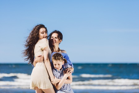 Mother, daughter and son hugging on the beach. Family time. Vacation.