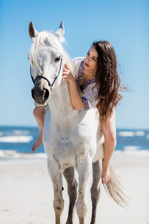 A portrait of a young girl sitting on a white horse on the beach. Bonding with animal. Stock Photo
