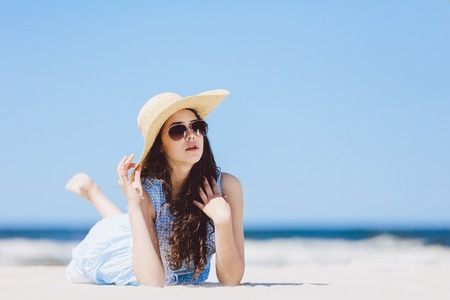 Young girl laying on the sandy beach in a straw hat and sunglasses. Summertime.