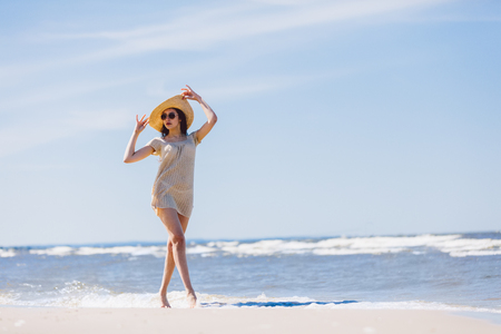 Young brunette girl in hat and sunglasses walking graciously on the beach. Summer by the sea.