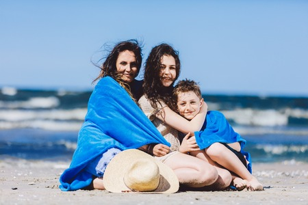 Mother, daughter and son sitting on a beach, wrapped in a blanket. Family vacation.