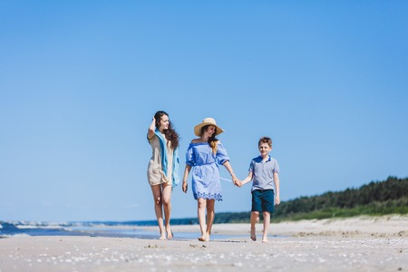 Mother and her two children walking on the beach. Family vacations. Stock Photo