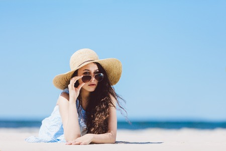 Pretty girl in straw hat laying on the sandy beach, holding her sunglasses. Summertime leisure.