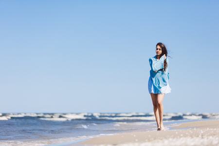Young girl walking by the sea, wrapped in a blue scarf. Summer relax.