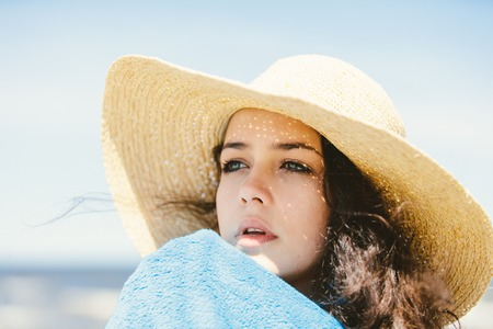 A portrait of a young girl in a straw hat. Close-up. Summer by the sea.