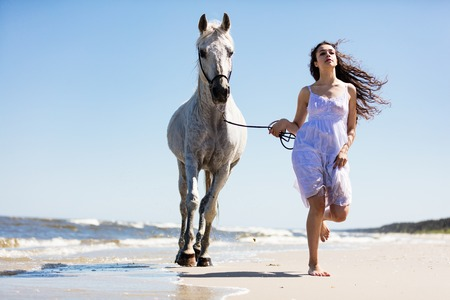 Young woman running on the beach, holding a white horse. Summertime. Freedom.