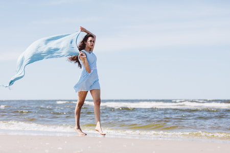 Pretty girl walking by the sea with a blue waving scarf. Summer by the sea. Stock Photo