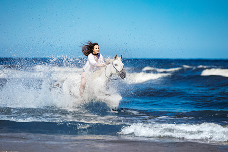 Girl on a white horse storming through the water on the seashore. Galopade. Horseback riding.