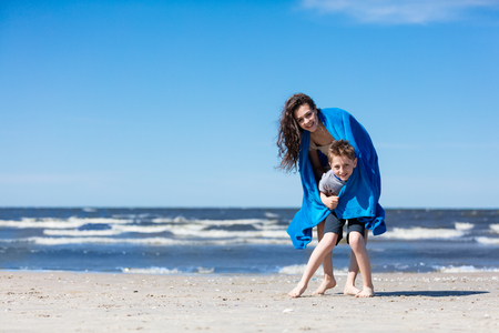 Older sister holding her little brother on the beach. Love and care. Happy sibling.