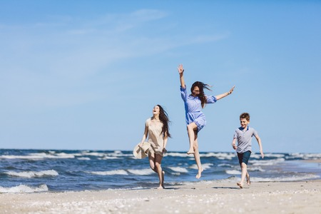 Happy family having a good time on the beach. Mother and her children. Summertime.