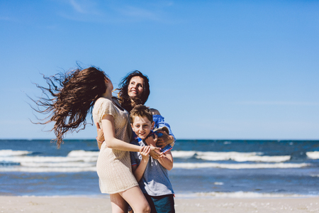 Mother and children hugging and standing on the beach by the sea. Family bonding. Stock Photo