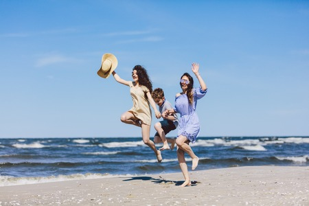 Mother and her children jumping high on the beach. Family vacations. Bonding. Stock Photo