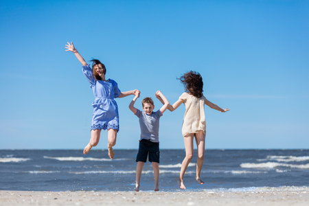Happy family jumping high on the seashore. Happiness. Mother and children. Stock Photo