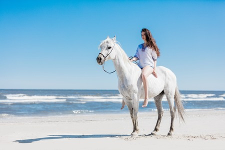 Girl sitting on a white horse by the sea on a sandy beach. Summer. Horseback riding.