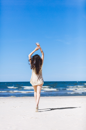 Young girl walking on the beach, holding her hands up. Vacation. Sunny beach. Stock Photo