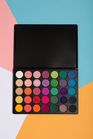 Makeup palette on a colorful geometrical background. Beauty products. Eyeshadows.