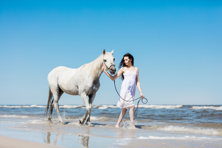 Girl in a white dress walking on the beach with white horse.