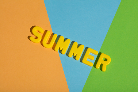SUMMER writing on a colorful pastel background made from yellow letters. Vacations.