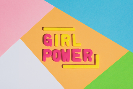GIRL POWER writing on a colorful pastel background made from plastic letters. Women empowerment.