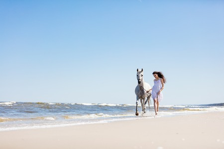 Young girl walking with white horse on the seashore. Summertime. Stock Photo