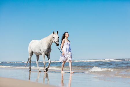 Young girl in white dress and white horse walking on the beach. Vacation. Stock Photo