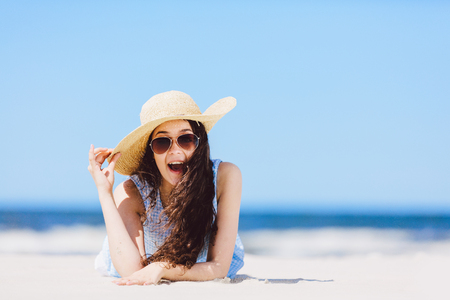 Young enthusiastic girl laying on the beach, smiling. Wow expression. Traveling. Summer. Stock Photo