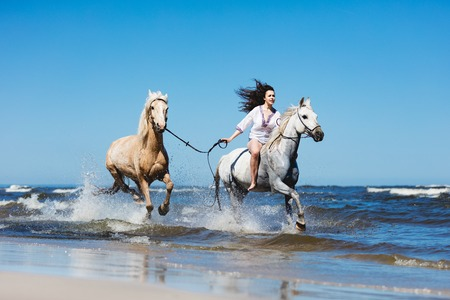 Girl galopading through the ocean waves with two horses. Wildness and freedom.