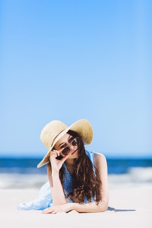 Young pretty woman in a straw hat laying on the beach, holding her sunglasses. Summertime leisure.