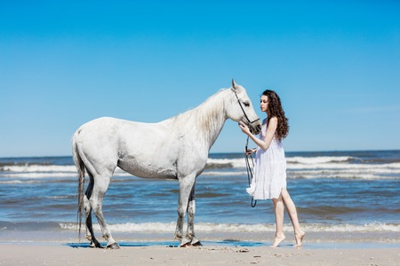 Young girl standing on the beach, touching white horses head. Creating a bond with animal.