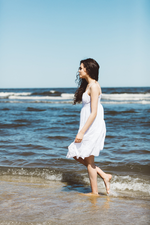 A girl in white dress walking alongside the ocean. Summer relax. Outdoor activities. Stock Photo